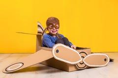 Piccola ragazza del sognatore che gioca con un aeroplano del cartone Infanzia Fantasia, immaginazione Fotografie Stock