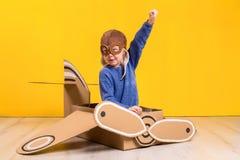 Piccola ragazza del sognatore che gioca con un aeroplano del cartone Infanzia Fantasia, immaginazione Fotografie Stock Libere da Diritti