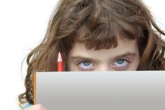 Piccola ragazza dell'allievo che osserva dietro il libro e la matita Immagine Stock