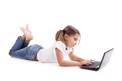 Piccola ragazza dell'allievo con un computer portatile Immagine Stock