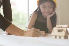 Piccola ragazza dell'ingegnere nel casco di sicurezza con una costruzione bl Fotografia Stock