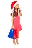 Piccola ragazza della Santa con i sacchetti che osservano in su Immagine Stock Libera da Diritti
