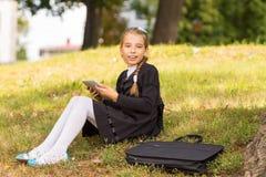 Piccola ragazza dello studente che si siede sull'erba e che per mezzo del PC della compressa Fotografie Stock
