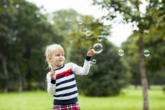 Piccola ragazza di gioco bionda con le bolle di sapone nella parità verde di estate Immagini Stock