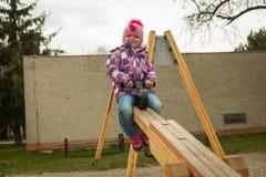 Piccola ragazza divertendosi sulle attrazioni dei bambini immagini stock libere da diritti