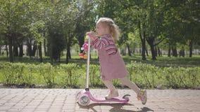Piccola ragazza divertente adorabile sveglia in vestito rosa che guida un motorino nel parco Macchina fotografica che segue il ba video d archivio