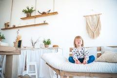 Piccola ragazza divertente che si siede nella cucina in uno stile rustico Mobilia strutturata leggera, sofà, tavola, macramè sull Fotografie Stock Libere da Diritti