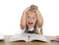 Piccola ragazza dolce della scuola che tira i suoi capelli biondi nello sforzo che ottiene pazzo mentre studiando Immagini Stock Libere da Diritti