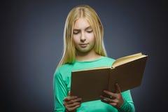 Piccola ragazza domandantesi bella con sorridere del libro isolato su fondo grigio Fotografie Stock