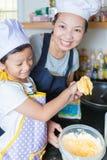 Piccola ragazza e madre asiatiche che producono pancake Fotografie Stock Libere da Diritti