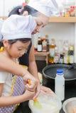 Piccola ragazza e madre asiatiche che producono pancake Immagine Stock Libera da Diritti