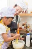Piccola ragazza e madre asiatiche che producono pancake Fotografia Stock Libera da Diritti