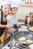 Piccola ragazza e madre asiatiche che producono pancake Immagine Stock