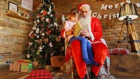 Piccola ragazza europea che si siede sulle ginocchia a Santa Claus video d archivio