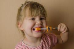 Piccola ragazza europea felice che pulisce i suoi denti fotografie stock libere da diritti