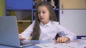 Piccola ragazza felice alla scuola che studing Immagine Stock Libera da Diritti