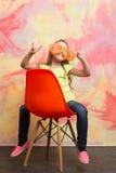 Piccola ragazza felice che indossa maglietta ed i vetri gialli sulla sedia Immagini Stock Libere da Diritti