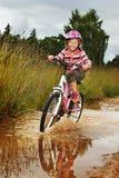 Piccola ragazza felice sulla bici fotografia stock