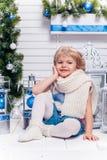 Piccola ragazza graziosa che si siede accanto ad un albero di Natale e ad un Christma fotografie stock