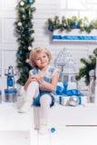 Piccola ragazza graziosa sorridente che si siede accanto ad un albero di Natale immagini stock libere da diritti