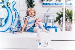 Piccola ragazza graziosa sorridente che si siede accanto ad un albero di Natale e fotografie stock