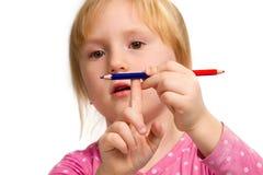 Piccola ragazza impressionabile con la matita blu e rossa immagine stock