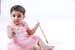 Piccola ragazza indiana/asiatica sveglia che gode della verniciatura con la carta, il pencle di colore e la spazzola di arte fotografia stock