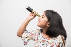 Piccola ragazza indiana che per mezzo del telescopio e studiando scienze spaziali immagini stock