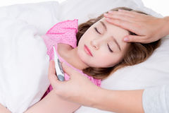 Piccola ragazza malata sveglia con un termometro. Fotografie Stock