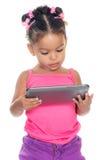 Piccola ragazza multirazziale che per mezzo di un computer della compressa Fotografie Stock