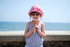 Piccola ragazza nei glasess e cappello del sole con il gelato Fotografie Stock Libere da Diritti