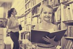 Piccola ragazza nell'età scolare che sta con il libro aperto Immagine Stock
