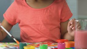 Piccola ragazza nera che fa un disegno sudicio con la pittura variopinta, bambino artistico stock footage