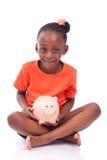 Piccola ragazza nera sveglia che tiene un porcellino salvadanaio sorridente - ch africano Fotografia Stock