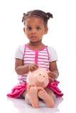 Piccola ragazza nera sveglia che tiene un porcellino salvadanaio sorridente - ch africano Fotografia Stock Libera da Diritti