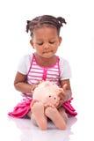 Piccola ragazza nera sveglia che tiene un porcellino salvadanaio sorridente - ch africano Immagini Stock
