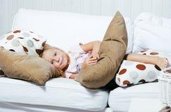 Piccola ragazza norvegese bionda sveglia che gioca sul sofà con i cuscini, concetto della gente di stile di vita Fotografia Stock Libera da Diritti