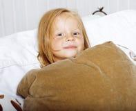 Piccola ragazza norvegese bionda sveglia che gioca sul sofà con i cuscini, concetto della gente di stile di vita Immagine Stock Libera da Diritti