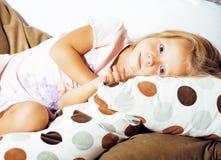 Piccola ragazza norvegese bionda sveglia che gioca sul sofà con i cuscini, solo domestico pazzo, concetto della gente di stile di Immagine Stock Libera da Diritti