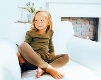 Piccola ragazza norvegese bionda sveglia che gioca sul sofà con i cuscini, solo domestico pazzo, concetto della gente di stile di Fotografie Stock Libere da Diritti