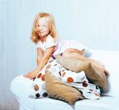 Piccola ragazza norvegese bionda sveglia che gioca sul sofà con i cuscini, solo domestico pazzo, concetto della gente di stile di Fotografia Stock Libera da Diritti