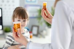 Piccola ragazza paziente sveglia divertendosi selezionando una bottiglia dei farmaci immagini stock