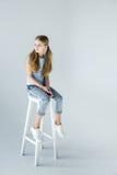 Piccola ragazza pensierosa alla moda che si siede sulla sedia fotografia stock libera da diritti