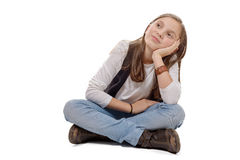 Piccola ragazza pensierosa che si siede a gambe accavallate su un fondo bianco Immagini Stock