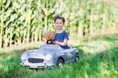 Piccola ragazza prescolare del bambino che conduce la grande automobile del giocattolo e che si diverte con il gioco con l'orso g Fotografia Stock Libera da Diritti