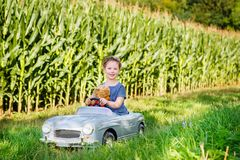 Piccola ragazza prescolare del bambino che conduce la grande automobile del giocattolo e che si diverte con il gioco con l'orso g immagine stock