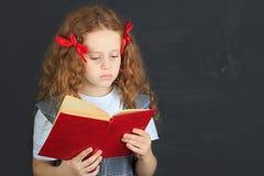 Piccola ragazza riccia che legge il libro Immagine Stock