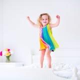 Piccola ragazza riccia sveglia del bambino che salta sul letto bianco Fotografie Stock