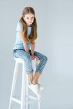 Piccola ragazza seria alla moda che si siede sulla sedia fotografia stock