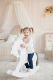 Piccola ragazza sorridente adorabile sul cavallo di legno del giocattolo all'interno di una stanza del bambino Fotografie Stock Libere da Diritti